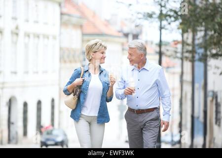 Glückliches Ehepaar mittleren Alters sahen einander haltend Eistüten in Stadt - Stockfoto