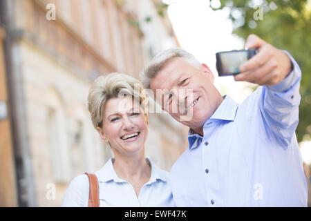 Fröhliches Paar mittleren Alters unter Selbstporträt im freien - Stockfoto