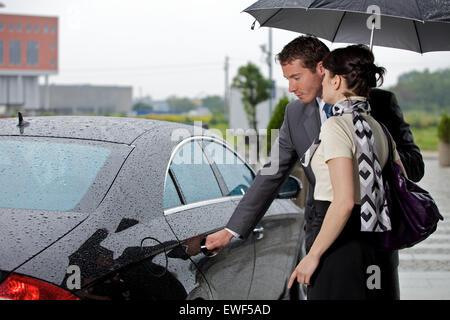 Junger Mann Türöffnung des Autos für die Frau - Stockfoto