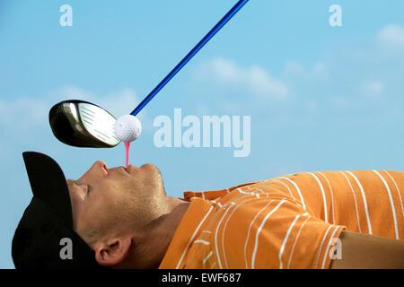 Mann Ausgleich Golfball am Abschlag in den Mund - Stockfoto