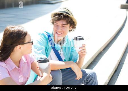 Glückliche Freunde halten Einweg Kaffeetassen auf Schritte im freien sitzend