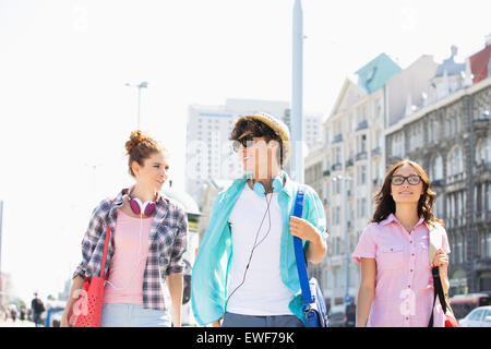 Glückliche Freunde sprechen während des Gehens in Stadt - Stockfoto