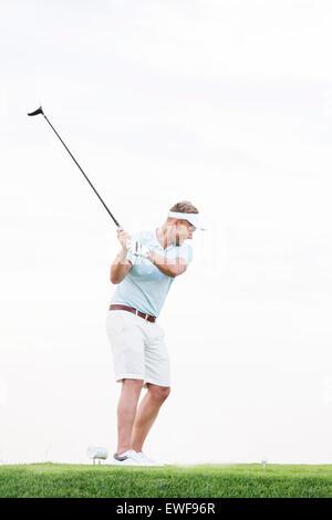 In voller Länge des mittleren Erwachsenenalter Menschen schwingen Golfclub gegen klaren Himmel - Stockfoto