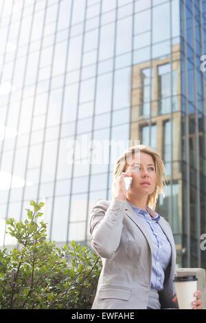 Geschäftsfrau mit Handy vor Bürogebäude - Stockfoto