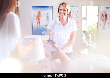 Lächelnd Physiotherapeut mit Ultraschallsonde am Bein des Patienten - Stockfoto