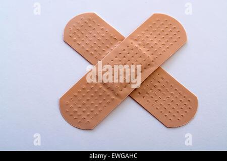 Bandage Kreuz auf weißem Hintergrund - Stockfoto