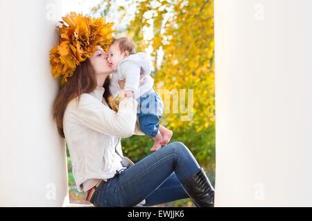 Attraktive junge Mutter mit Ahorn Blätter Kranz sitzen zwischen zwei Säulen, die ihr Baby küssen - Stockfoto