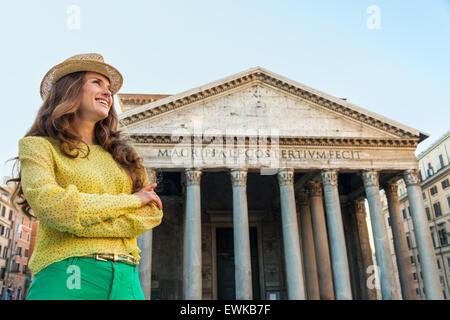 Eine junge Brünette Frau lächelt, als sie sieht in die Ferne, Arme verschränkt, mit dem Pantheon in Rom im Hintergrund. - Stockfoto