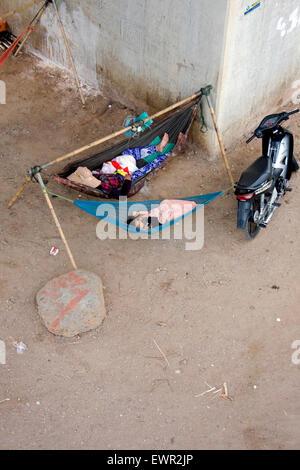 Eine Frau und ein Kind schlafen in Hängematten unter einer Brücke in Kampong Cham, Kambodscha. - Stockfoto