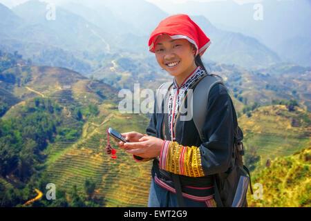 Hmong Mädchen Tourguide auf ihrem Handy in Sapa, Vietnam über Reisfelder. - Stockfoto