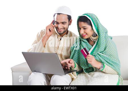 2 indischen Muslim verheiratet paar Laptop Kreditkarte einkaufen - Stockfoto