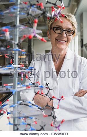 Porträt lächelnd Wissenschaftler hinter Molekül Modell im Labor - Stockfoto