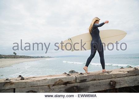 Weibliche Surfer mit Surfbrett zu Fuß am Strand Steg - Stockfoto
