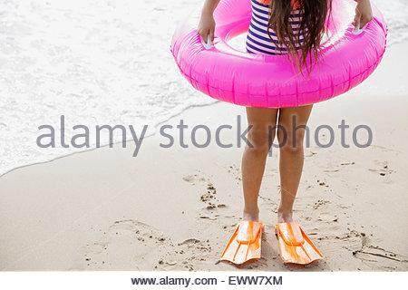 Mädchen im aufblasbaren Ring und Flossen am Strand - Stockfoto