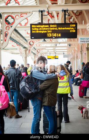 Nach Hause für den Sommer: ein junges Paar junge Mädchen Mann Frau Studenten umarmen, während sie auf ihren Zug - Stockfoto