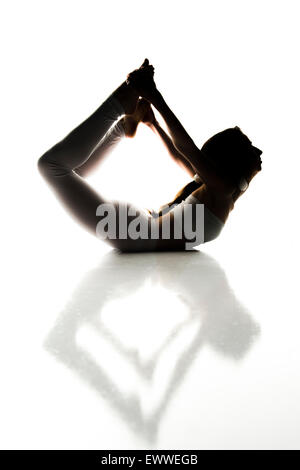 Eine junge schlanke Fit gesund geschmeidig Frau trägt weißes bauchfreies Top und Leggings (eng anliegende Yoga Hose) - Stockfoto