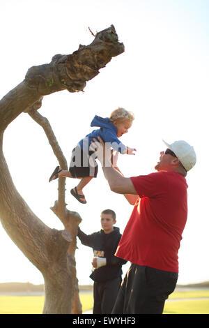 Vater fangen Sohn springen aus einem Baumstamm mit jungen im Hintergrund - Stockfoto