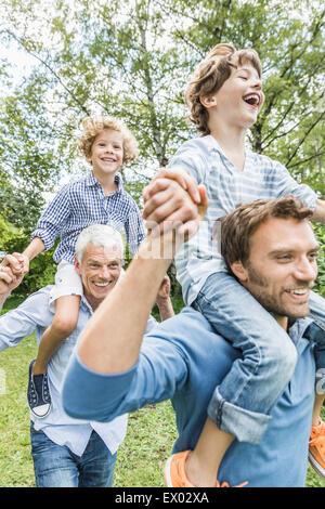 Mitte erwachsener Mann mit Vater geben Söhne Schulter tragen Sie im Garten - Stockfoto