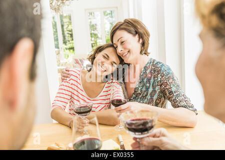Vier Erwachsene Freunde trinken Rotwein zusammen am Esstisch - Stockfoto