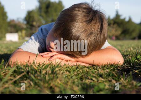 Mürrisch junge mit Kopf nach unten liegend auf Park Rasen - Stockfoto