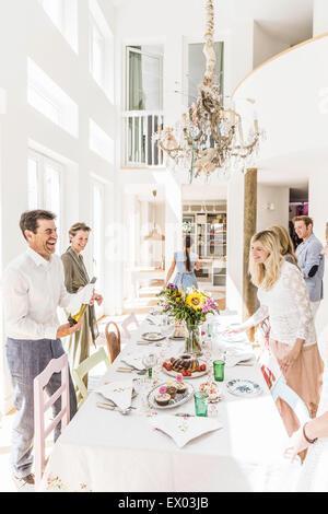 Familie, lachen, während die Zubereitung von Esstisch für party - Stockfoto