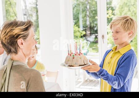 Junge Übergabe Geburtstagskuchen an Großmutter im Speisesaal - Stockfoto
