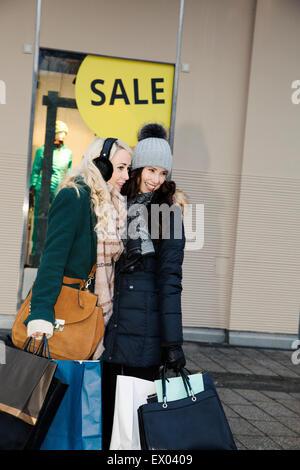 Zwei Frauen mit Einkaufstaschen im Winterschlussverkauf - Stockfoto