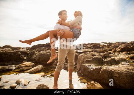 Junger Mann mit Freundin über Felsen-Pool am Strand - Stockfoto