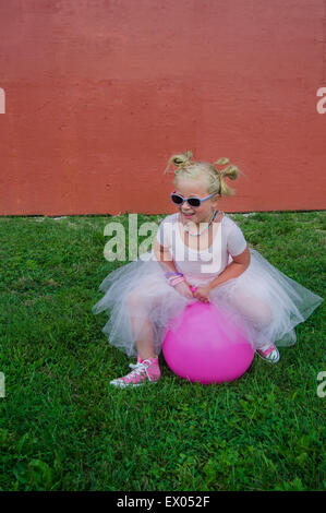 Junge Mädchen tragen Tutu, Prellen auf rosa aufblasbare Trichter - Stockfoto