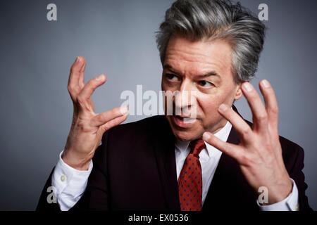 Studioportrait von reifer Geschäftsmann mit Händen öffnen in Erläuterung - Stockfoto
