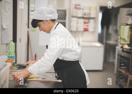Baker rollenden Teig in Küche - Stockfoto