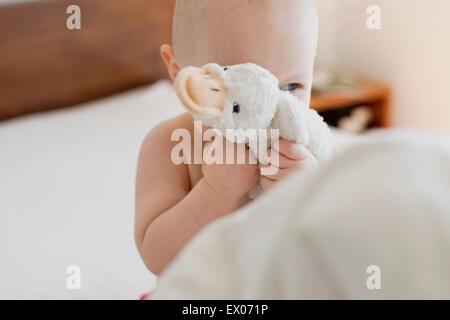 Babymädchen im Bett versteckt sich hinter Stofftier sitzend - Stockfoto