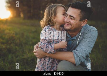 Mädchen küssen Vater auf Wange im Feld - Stockfoto