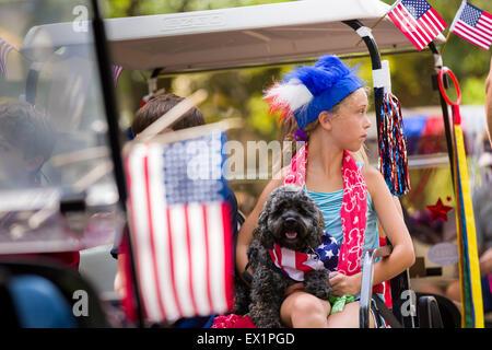 South Carolina, USA. 4. Juli 2015. Ein junges Mädchen in patriotischen Kostüm hält ihren Hund während der I'On Nachbarschaft - Stockfoto