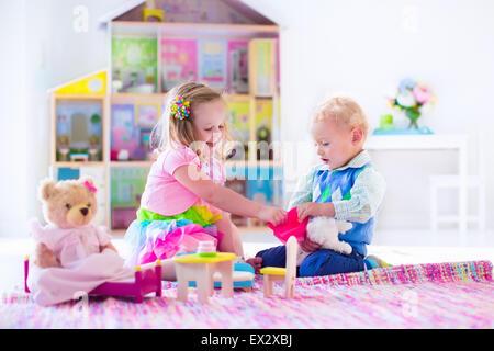 Kinder spielen mit Puppenhaus und tierischen Plüschtiere. Kinder sitzen auf einem rosa Teppich im Spiel zu Hause - Stockfoto