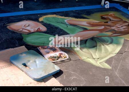 Eine unvollendete Porträt einer jungen Frau hält ein Rehkitz an der jährlichen Imadonnari Street Painting Festival - Stockfoto