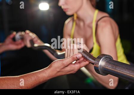 Hand von Trainer helfen junge Frau Aufzug Gewicht - Stockfoto