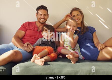 Eltern mit Kindern draußen zu sitzen, auf der Couch im Hinterhof. Glückliche junge Familie entspannt auf der Terrasse, - Stockfoto