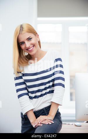 Glückliche junge Frau sitzt auf dem Tisch im Büro - Stockfoto