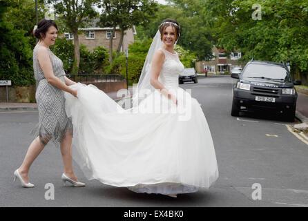 Schöne junge Frau Braut im weißen Kleid an ihrem Hochzeitstag von ihre Brautjungfer Straßenseite geholfen - Stockfoto
