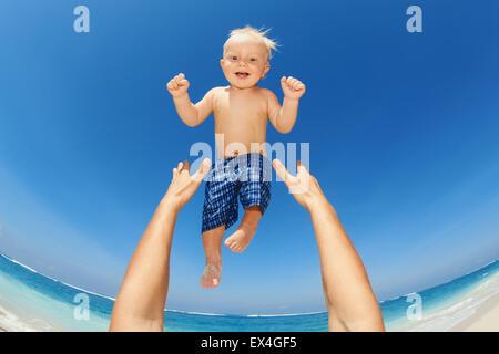 Hände des Vaters warf sich hoch in der Luft Babyjungen am Weißen Meer Sand Strand. Im freien gesundes Kind Aktivität, - Stockfoto