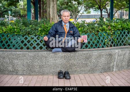 Chinesische älterer Mann meditierend in Hong Kong, China - Stockfoto
