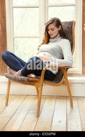 Schwangere Frau sitzt auf Sessel halten den Bauch - Stockfoto