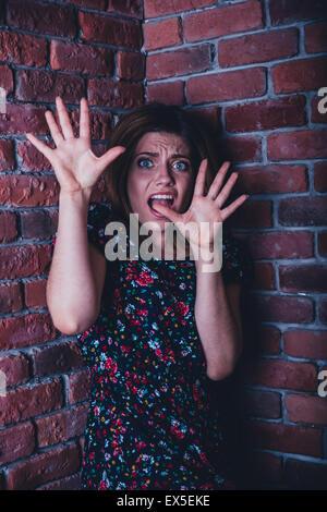 Verängstigte junge Frau steht in der Ecke der Mauer - Stockfoto