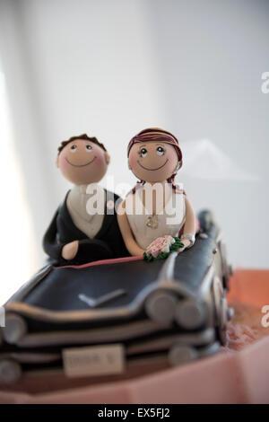 Süße Hochzeitstorte Figuren mit Braut und Bräutigam Figurinen im Cabrio - Stockfoto