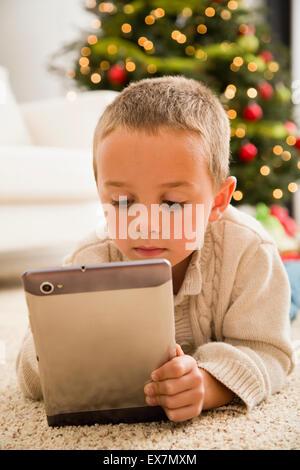 Junge (6-7) mit digital-Tablette auf Teppich liegend - Stockfoto