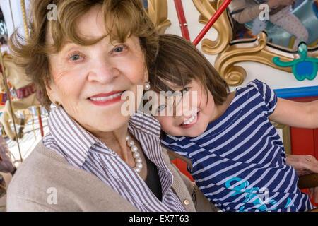 Kleinkind Mädchen mit ihrer Urgroßmutter auf dem Karussell, San Diego, Kalifornien - Stockfoto