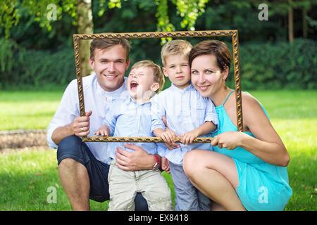 Porträt der jungen, fröhlichen Familie posiert im Garten - Stockfoto