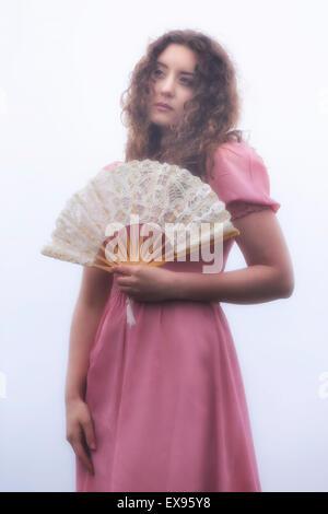 eine schöne Frau mit langen lockigen Haaren in einem rosa Kleid mit einem weißen Lüfter - Stockfoto
