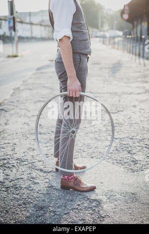 Nahaufnahme von Beinen Schuhe Hipster Mann mit alten Fahrrad-Rad in der Stadt - Stockfoto